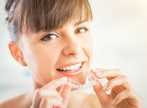 Fairfield cosmetic dentist woman putting on Invisalign braces