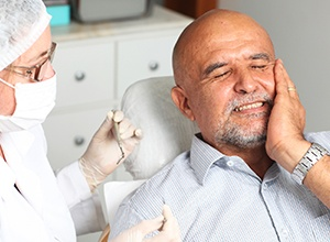 man in dental chair in pain holding cheek