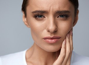 sad woman in dental pain holding cheek
