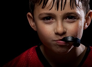 little kid holding athletic mouthguard with mouth