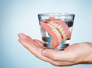 hand holding dentures in a glass of water